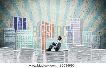 Thoughtful businessman looking away while sitting on pile of documents with drawn cityscape on background. Mixed media.
