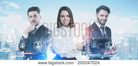 Three business partners two men and a woman are standing together and portraying success in a morning city. A network hologram is in the foreground. Toned image double exposure