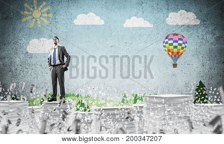 Confident businessman in suit standing on pile of documents among flying letters with drawn landscape on background. Mixed media.