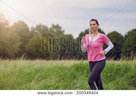 Fit middle-aged woman running through a rural field listening to music on her mobile phone using earbuds looking to the side with a happy smile in a healthy outdoors lifestyle concept