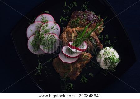 Meat fried on a plate with vegetables on a black background