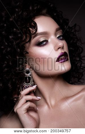 Beauty young woman with curly small and long hair. Permed hair. Glamour lady, Beautiful Girl on gray background. Portrait. Wavy Hair, perfect make up. Closed eyes.