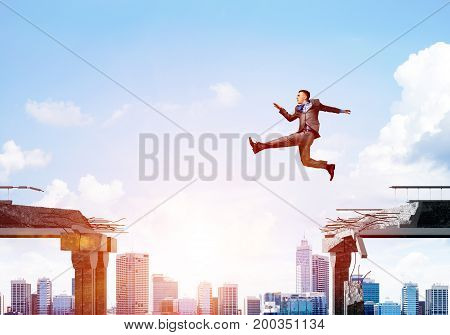 Businessman jumping over gap with flying letters in concrete bridge as symbol of overcoming challenges. Cityscape with sunlight on background. 3D rendering.