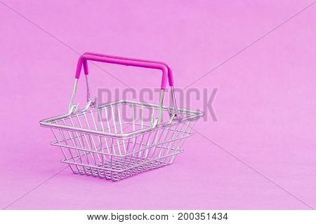 Miniature shopping basket, alone on purple background