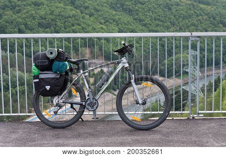 Mountain bike with saddlebags on the water dam. Camping equipments is mounted on the bike.