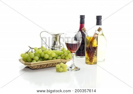 Bottles of wine, pitcher, wineglass and grapes on a white background closeup