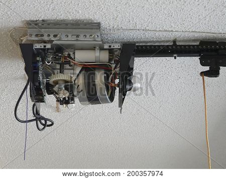 Close-up of an automatic garage door opener motor gear drive needing repair at a residence.