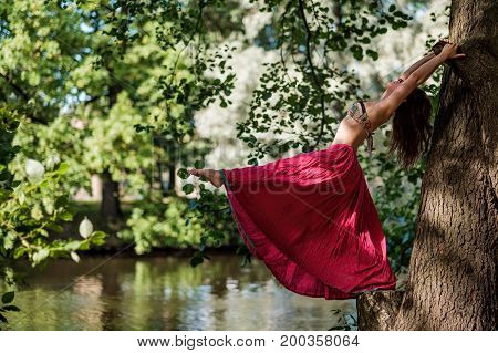 Caucasian woman wearing red skirt in forest holding tree doing yoga asana