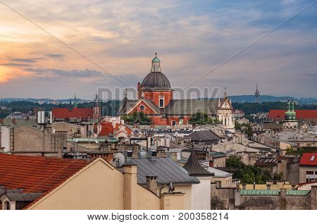 Roofs of the houses and the church in sunset time. Krakow. Poland
