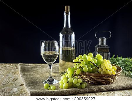 Bottles of wine, wineglass and grapes on a black background closeup