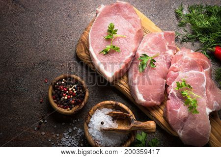 Fresh meat. Raw pork steak on a cutting board with herbs and spices. Top view copy space.