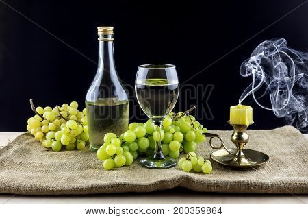 Bottle with table wine, wineglass and grapes on a black background closeup