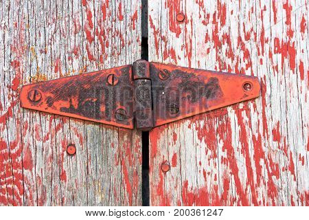 A close up image of an old vintage door hinge covered in red paint and rust.