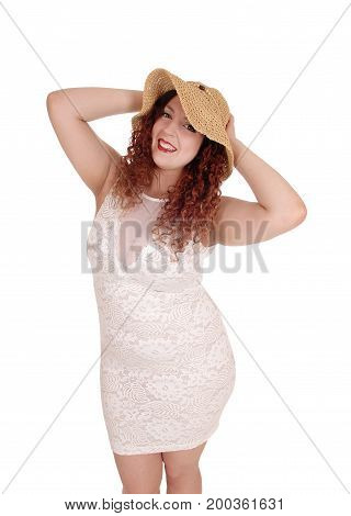 A young pretty woman in a beige dress and straw hat standing and smiling with her hands on her hat isolated for white background