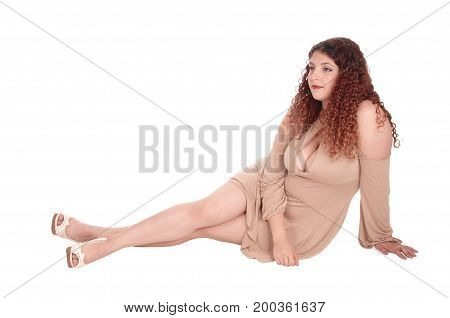 A beautiful woman in a beige dress sitting on the floor with her long curly brunette hair looking away isolated for white background.