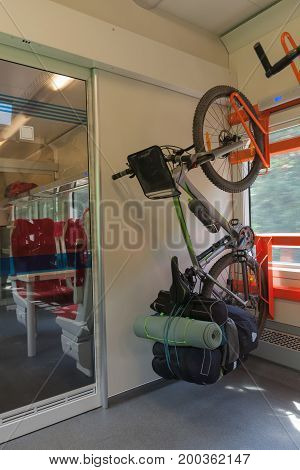 Mountain bike with saddlebags is transported in public transportation inside in the train.