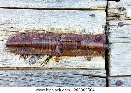 A close up image of an old rusted metal door latch.