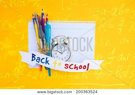 back to school concept - alarm clock and school supplies on ruled paper with back to school text on paper ribbon with math formulas