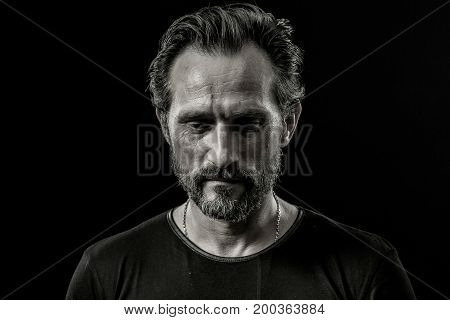 Black and white close up portrait of a severe man with sad facial expression. Male showing painful emotion on a black background.
