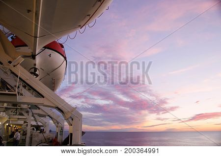 A white lifeboat on  cruise-ferry ship under sky