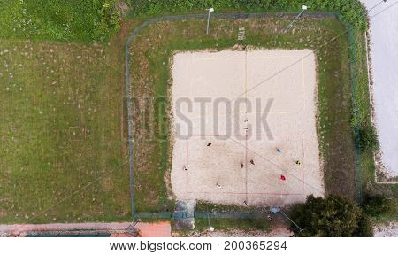 Aerial view of people playing beach volleyball. Popular team sport during picnics.