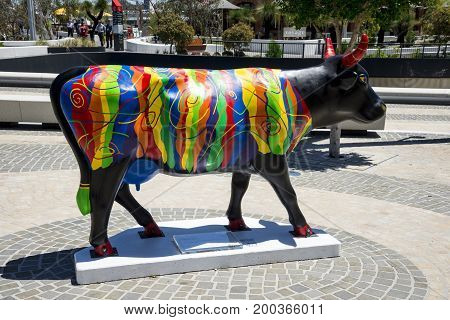 WESTERN AUSTRALIA, PERTH - NOVEMBER 2016: Colorful strip painted black cow near Bell Tower as part of CowParade event