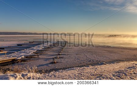 Winter landscape showing ice covered ocean and marina for small boats, frozen. blue sky and white snow Norway, Fredrikstad, Ora Nature Reserve.