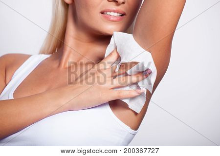 Hygiene - young woman wiping the armpit with wet wipes perspiration sweat