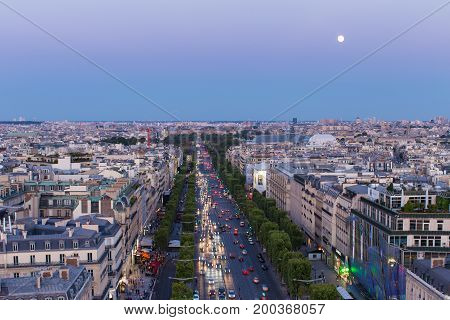 The moon rises above the Champs-Elysees in Paris
