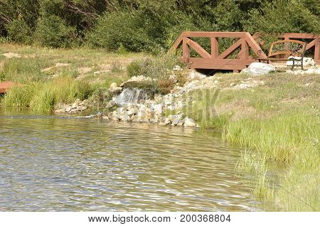 small waterfall into a pond. There is a red wood bridge by the waterfall and a park bench. The pond is surrounded by trees and bushes