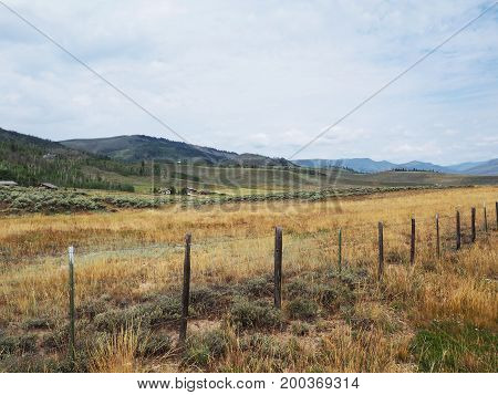 prairie and a simple wire fence in Colorado with hills in the background