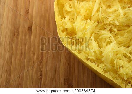Closeup on a roasted spaghetti squash on a wooden board