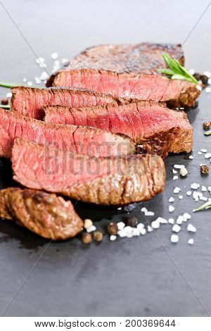 medium rare grilled steak sliced up with salt and pepper