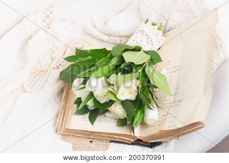 Old open book with hanwritten old letters and white flowers on romantic lace background