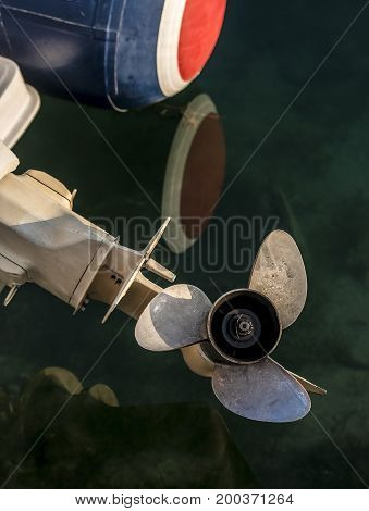 Boat propeller sticking out of sea water.