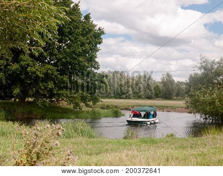 A Boat Going Down A River Outside In England Country Summer