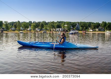 St-Gabriel-de-Brandon Canada-20 July 2017 : woman kayaking alone at Maskinonge Lake at summer time in front of the beach