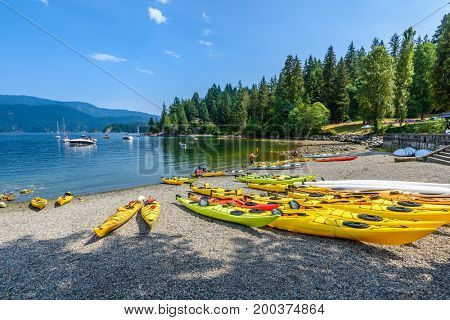 Canoe, kayak and luxury yachts in the bay of Deep Cove, Vancouver, Canada.