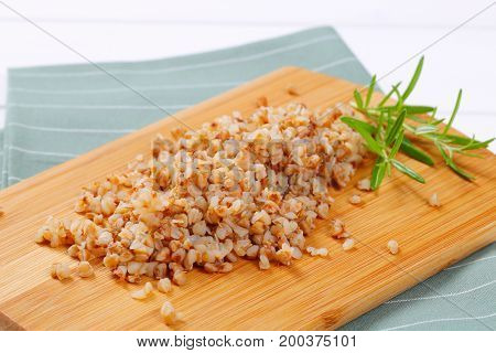 pile of cooked buckwheat on wooden cutting board - close up