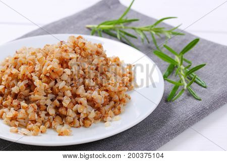 plate of cooked buckwheat on grey place mat - close up