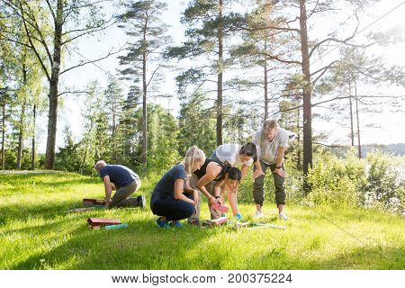 Friends Playing With Building Blocks On Grassy Field