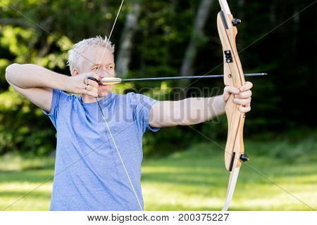 Male Athlete Aiming With Bow And Arrow In Forest