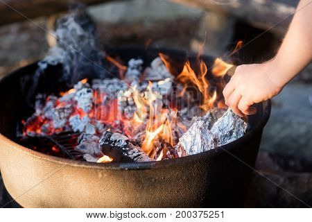 Closeup Of Hand Grilling Food Wrapped In Foil On Firepit
