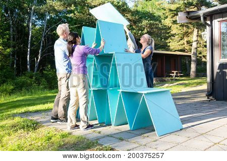 Friends Making Pyramid With Wooden Planks On Patio In Forest