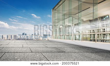 empty floor front of glass house with cityscape of hangzhou in cloud sky