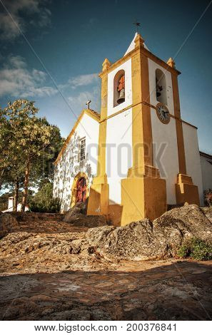 Little yellow and white church in rural village of Alter Pedroso, Portugal
