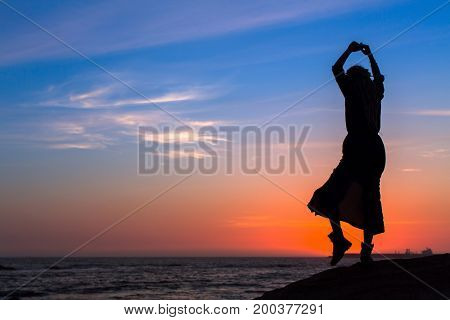 Silhouette woman activity on the sea beach at sunset.