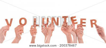 People putting hands in air together with word made of wooden letters on white background. Volunteering concept