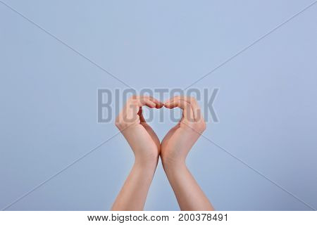 Heart shape made by raised hands on light background. Volunteering concept