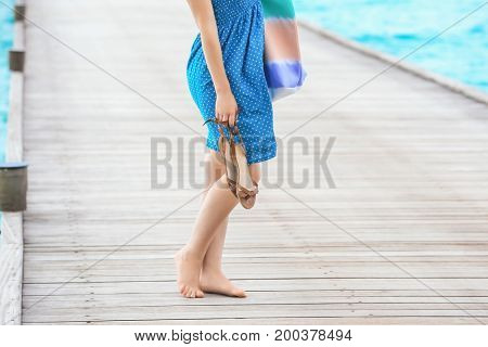 Beautiful young woman on pontoon at sea resort